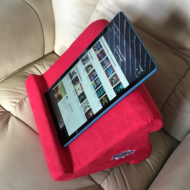 Photo of Flippy tablet pillow stand on a leather recliner, holding a Fire HD 10 in portrait orientation