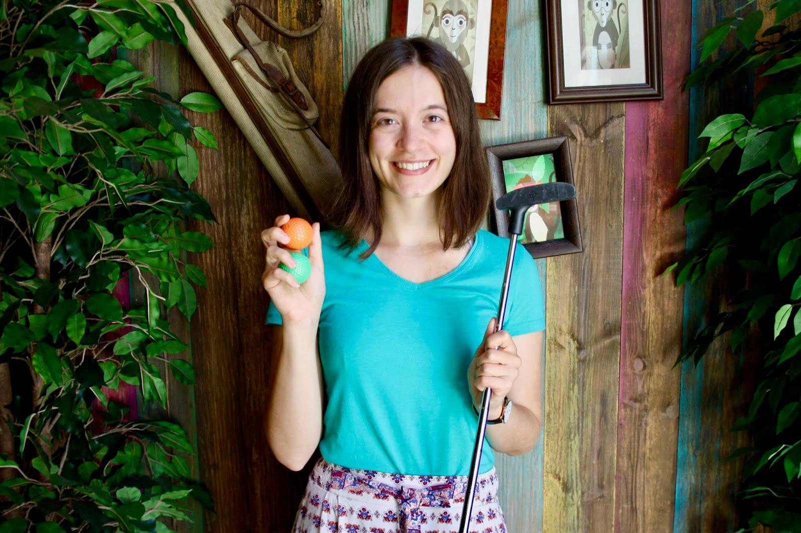 Abbey, holding a golf club and two golfballs, stands in front of a jungle themed backdrop at Treetop Adventure Golf, Leicester
