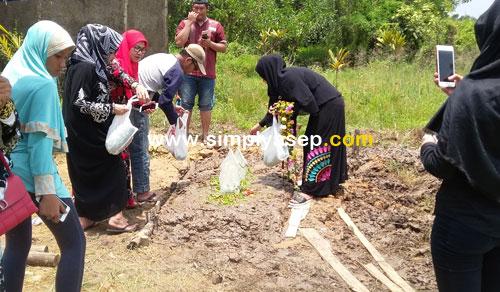 BUNGA : Prosesi pemakaman sudah selesai, keluarga yang berduka diberi kesempatan untuk menyampaikan doa dan menaburkan bunga di pusara anggota keluarganya. Jamaah dan para pengantar pun mulai meninggalkan lokasi ini . Foto Asep Haryono