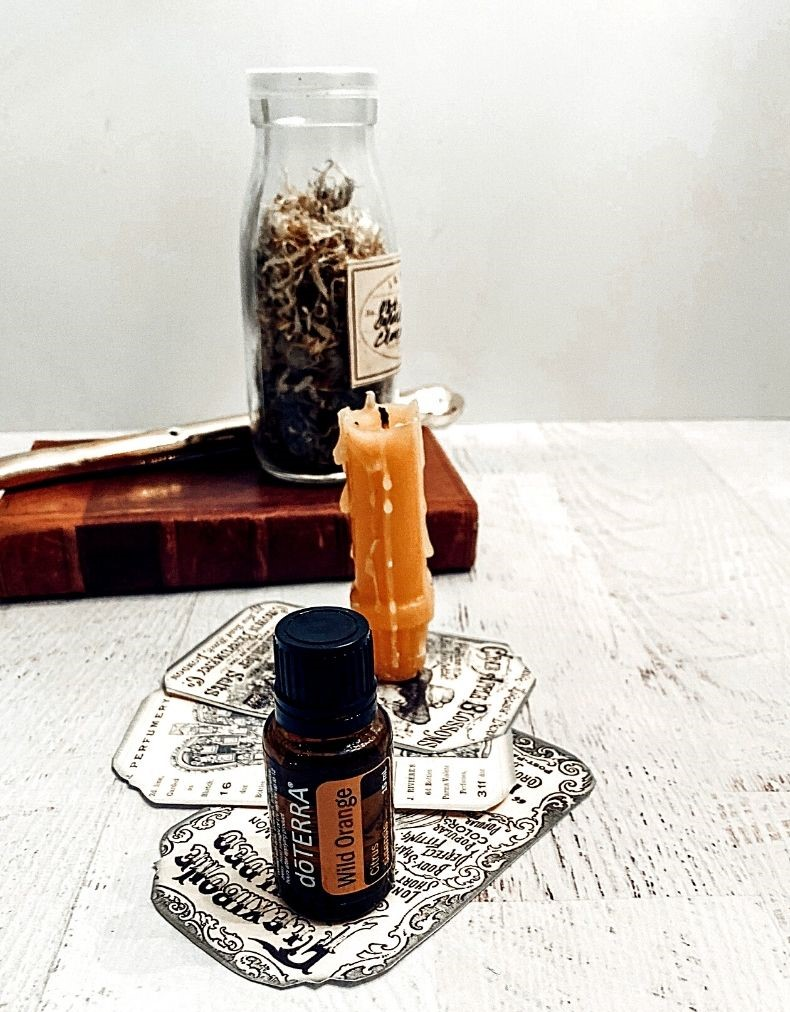 Calendula Bottle on book candle and Essential Oil