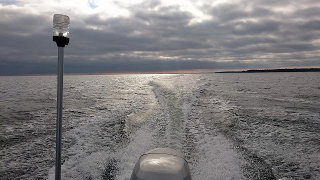Veneen perämoottori ja veneen jättämä vana vedessä.