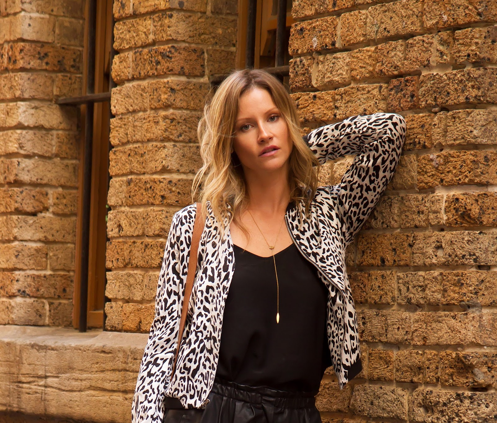 fashion and travel blogger, Alison Hutchinson, is wearing a leopard print bomber with a black silk camisole and leather shorts in Sydney CBD backstreets