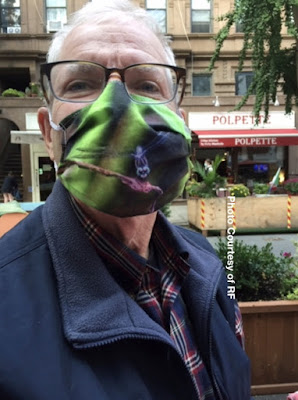 This photo features a man standing on a street located in NYC's UWS. He is wearing a face-mask that I designed for PPE during the COVID-19 pandemic. The mask he is wearing has a picture of a blue-colored dragonfly who I saw in Central Park at Turtle Pond. The background of the photo is green due to the foliage where the dragonfly was located. Information (both specifics re the materials used to make this mask as well as purchase info can be found through my website @ https://patriciayoungquist.com/Pages/store/FAAmasks.html).