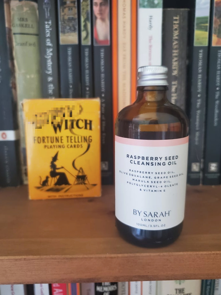 Raspberry Seed Cleansing Oil from By Sarah London on a bookshelf surrounded by books and a vintage deck of playing cards