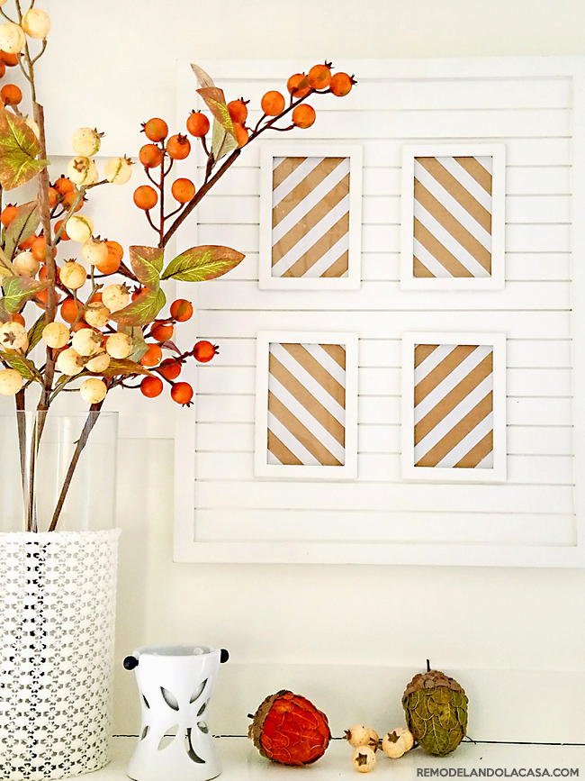 white fireplace mantel with fall branches and brown and white strips wall decor and acorns