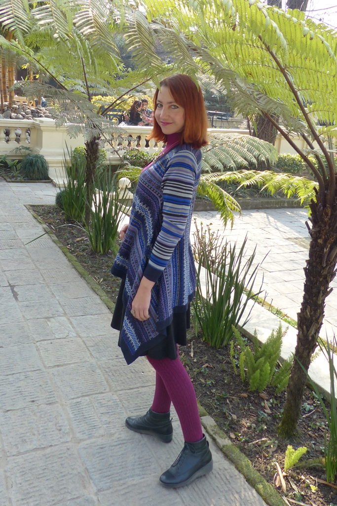 Patterned long sides cardigan worn over a skirt