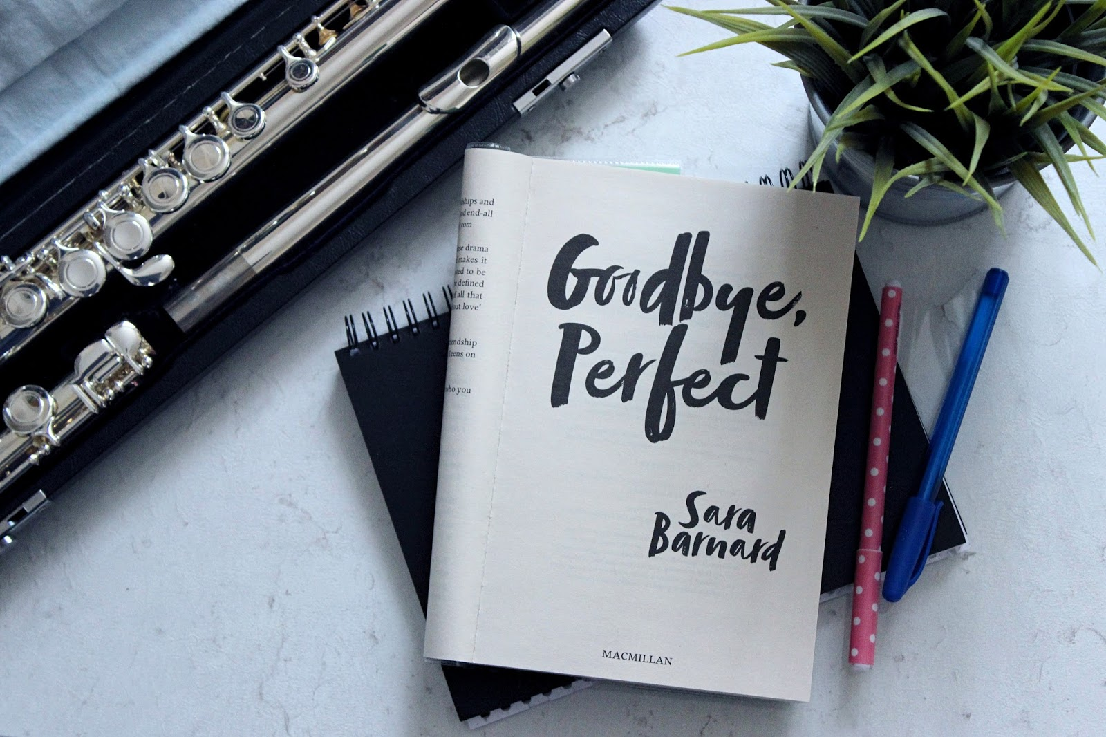 "An open copy of ""Goodbye,Perfect"" is in the centre balanced on a notebook, with two pens next to it. In the top right corner is a fake plant, and in the top left is a flute in an open case."