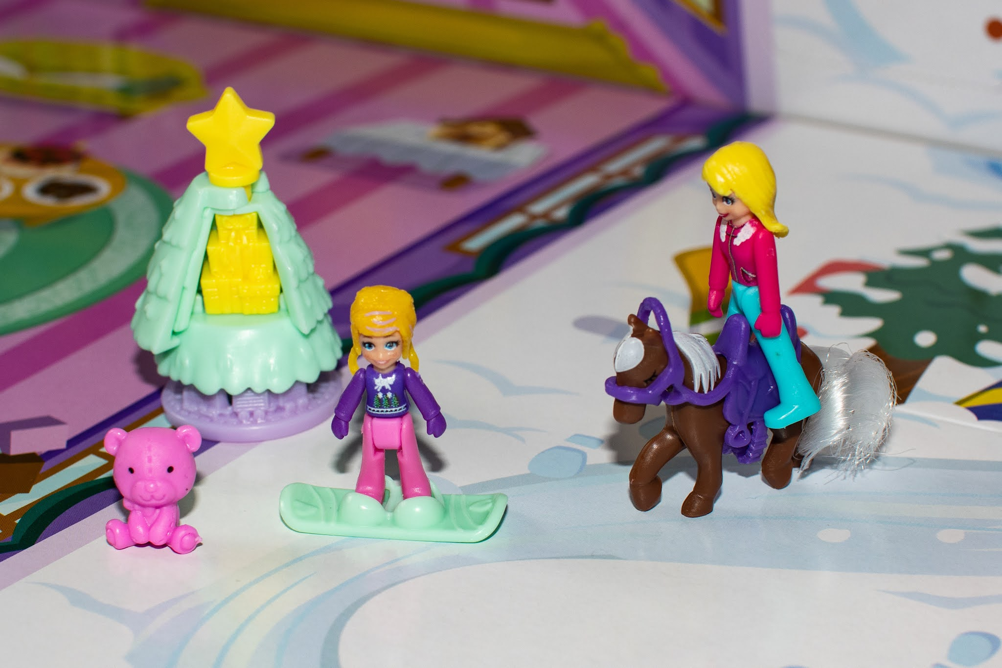 Some of the contents of the Polly Pocket Advent Calendar including a Christmas tree, a teddy and doll in ski's and a doll on a pony