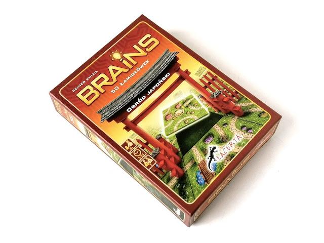 na zdjęciu pudełko od łamigówki Brains, na którym widać drewnianą bramę, wejście do ogrodu japońskiego