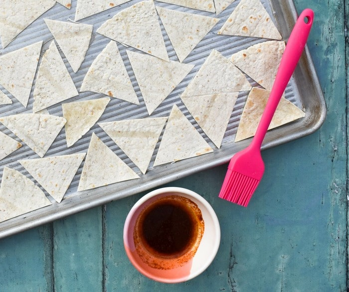 triangles or tortilla on a baking sheet with flavouring and a pastry brush
