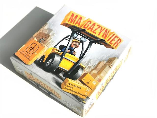 na zdjęciu pudełko gry Magazynier w kolorze białym z wizerunkiem uśmiechniętego magazyniera w kasku i z wąsem, jadącego wózkiem widłowym i wiozącego paletę ze skrzynkami, na których jest napis Magazynier