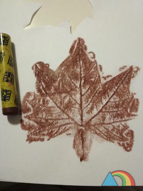 Silueta de una hoja seca, calcada pintando con cera de color marrón sobre una hoja de papel
