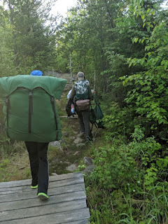 Two youth hiking through the woods with camping gear