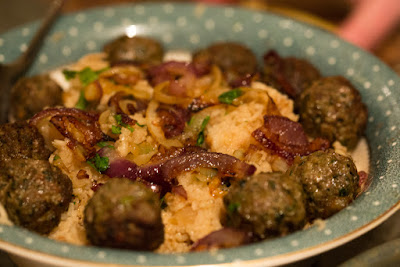 A bowl of brown onion pulao with sheekh kebab balls on top