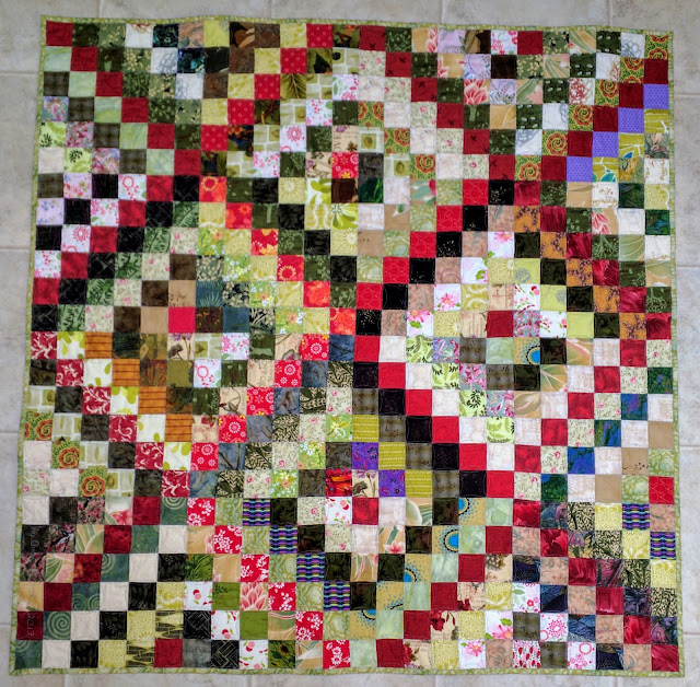 Scrappy Trip Around the World quilt in greens with red diagonals