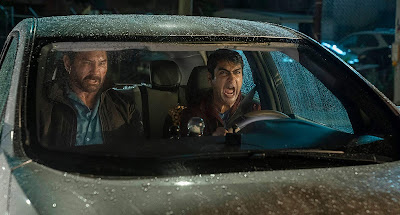 Kumail Nanjiani screams at Dave Bautista inside his Uber in a movie still for the new action film Stuber