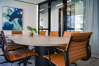 an empty conference room; tan chairs around a white table with some abstract art on the wall