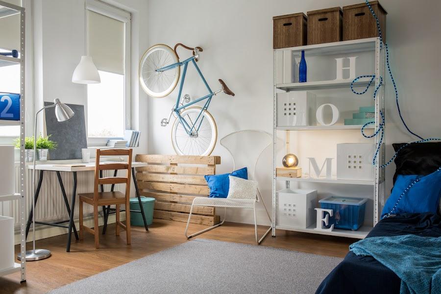 Habitación juvenil con estanterías metálicas, palets y una decoración low cost