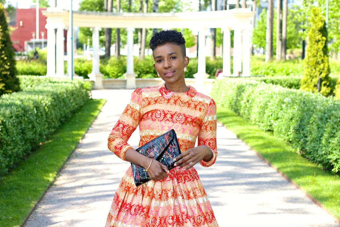 woman wearig red african print oufit with clutch bag in hand