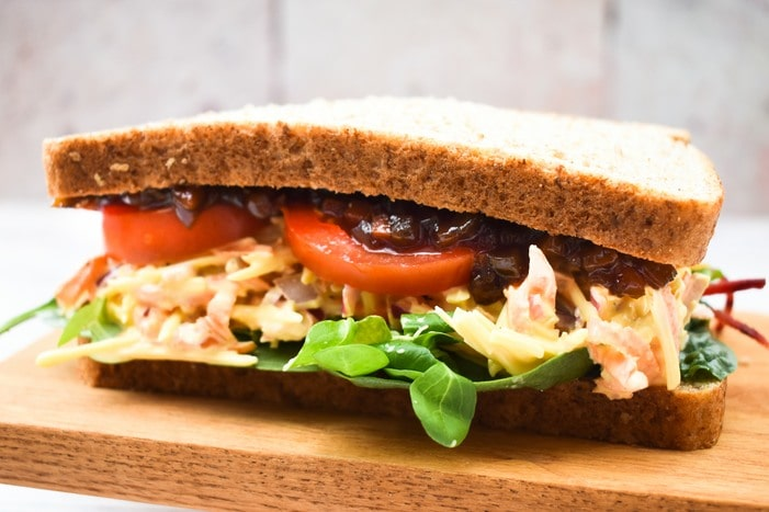 A cheese savoury sandwich with salad leaves, slices of tomato and pickle on a wooden board