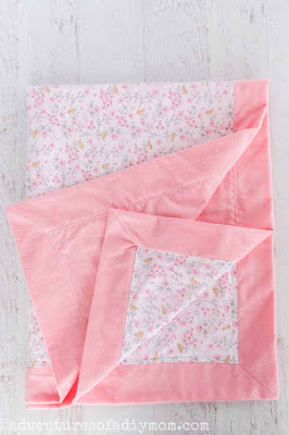 baby blanket with pink border.