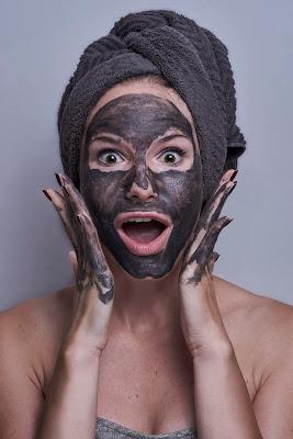 Mujer con mascarilla facial y cara de sorpresa