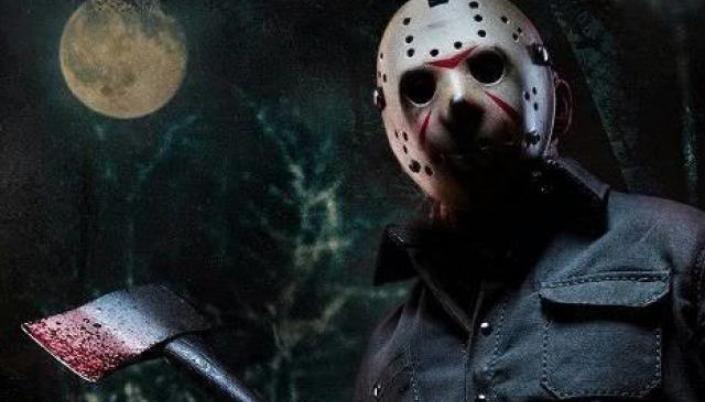 Imagem: Personagem Jason, de sexta-feira 13. Um Homem de grande porte, que usa macacão industrial, o rosto é coberto por uma mascara branca de hóquei, que está gasta. Ele segura um machado ensanguentado. O fundo atrás é uma floresta em noite de lua cheia.