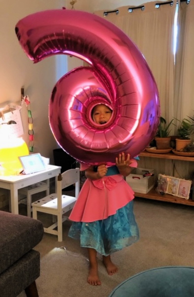 Little girl with the number 6 balloon