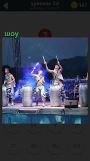 На сцене происходит шоу, молодые люди бьют в барабаны и исполняют музыку