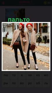 две девушки стоят в одинаковых пальто серого цвета