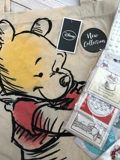 Canvas Pooh bag with some of the items to the side of the picture