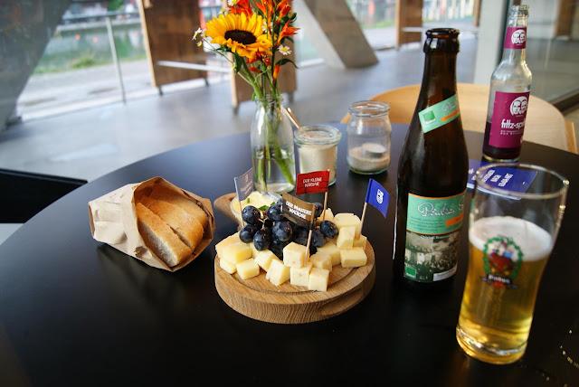Ein gedeckter Tisch mit einem Käsebrett und zwei Getränkeflaschen