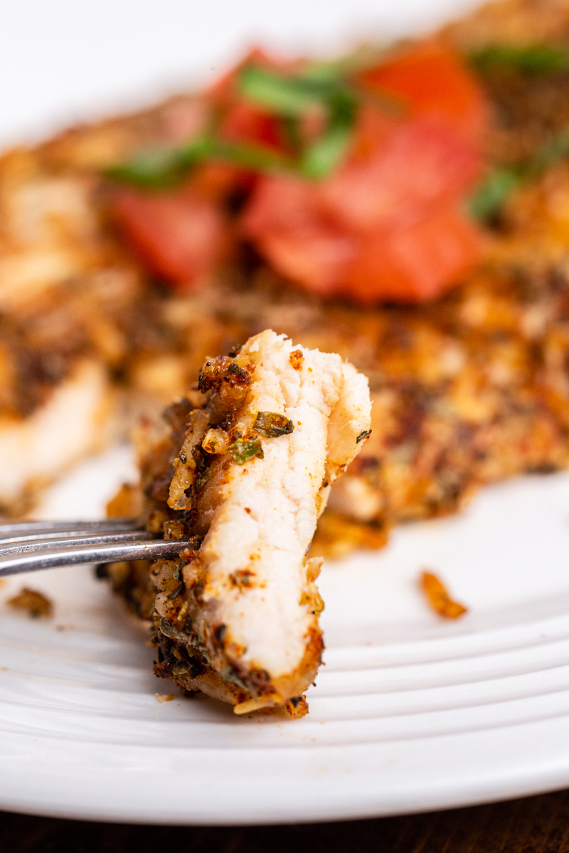 Closeup photo of a bite of Keto Parmesan Chicken Cutlet on a fork with the rest of the cutlet on a white plate in the background.