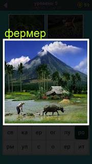 на ферме трудится мужчина с быком на фоне своего дома и горы 667 слов