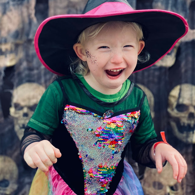 Little dresses as a witch with a green gecko t-shirt on under the dress. She has glitter on ger face and she is pulling a face like she is cackling