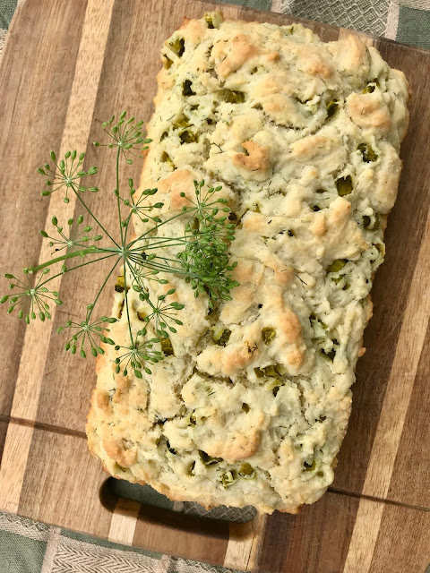 Loaf of baked dill pickle quick bread on a cutting board.