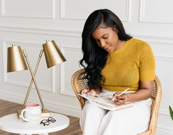 Mulher negra sentada em uma sala com paredes brancas e decoração clean escrevendo em uma agenda