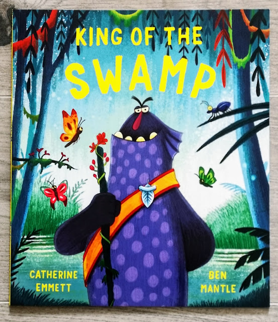 Image of the front cover of a childrens book entitled King of the Swamp by catherine emmet and ben mantle. The image shows a swamp with trees and butterflies and in the centre is a creature that is smiling and wearing a crown.