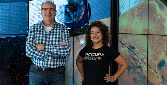 Dr. Edwin Mierkiewicz, associate professor of Physics, and Andréa Hughes, a Ph.D. candidate, pose with an image of NASA's MAVEN spacecraft. Photo: Embry-Riddle/Daryl LaBello