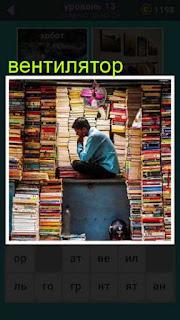 сидит мужчина в большом количестве книг и сверху висит вентилятор