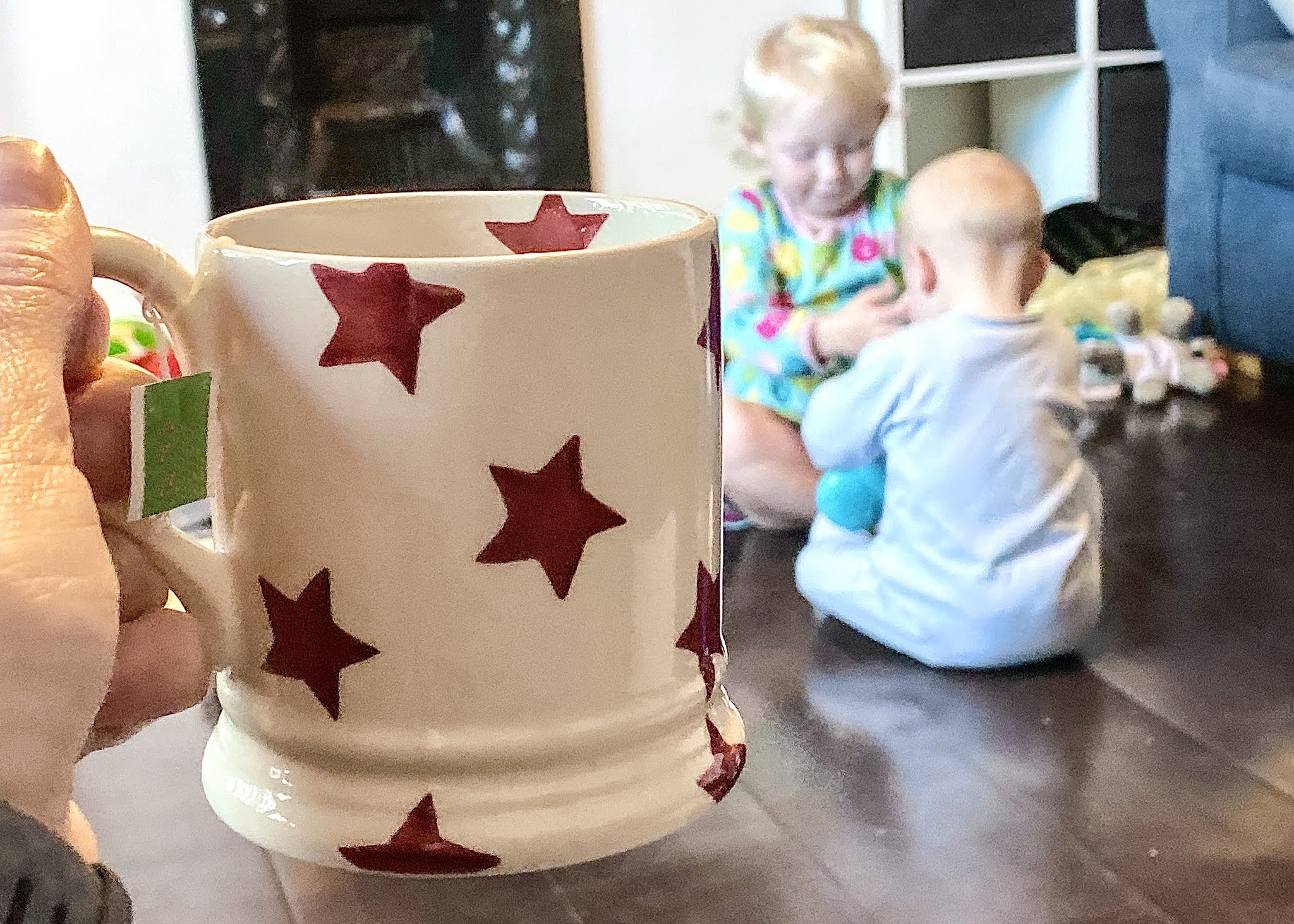 A cup of tea being held with children playing in the background in a low maintenance to clean and tidy house