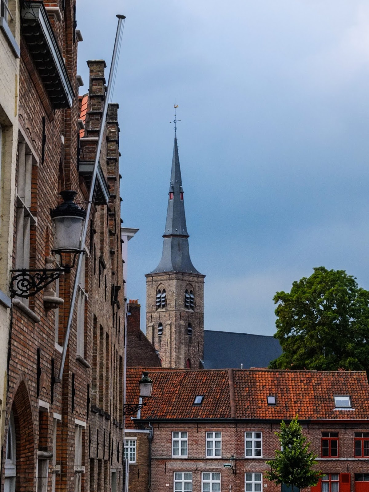St. Anna's Church spire showing behind buildings in Bruges, Belgium.