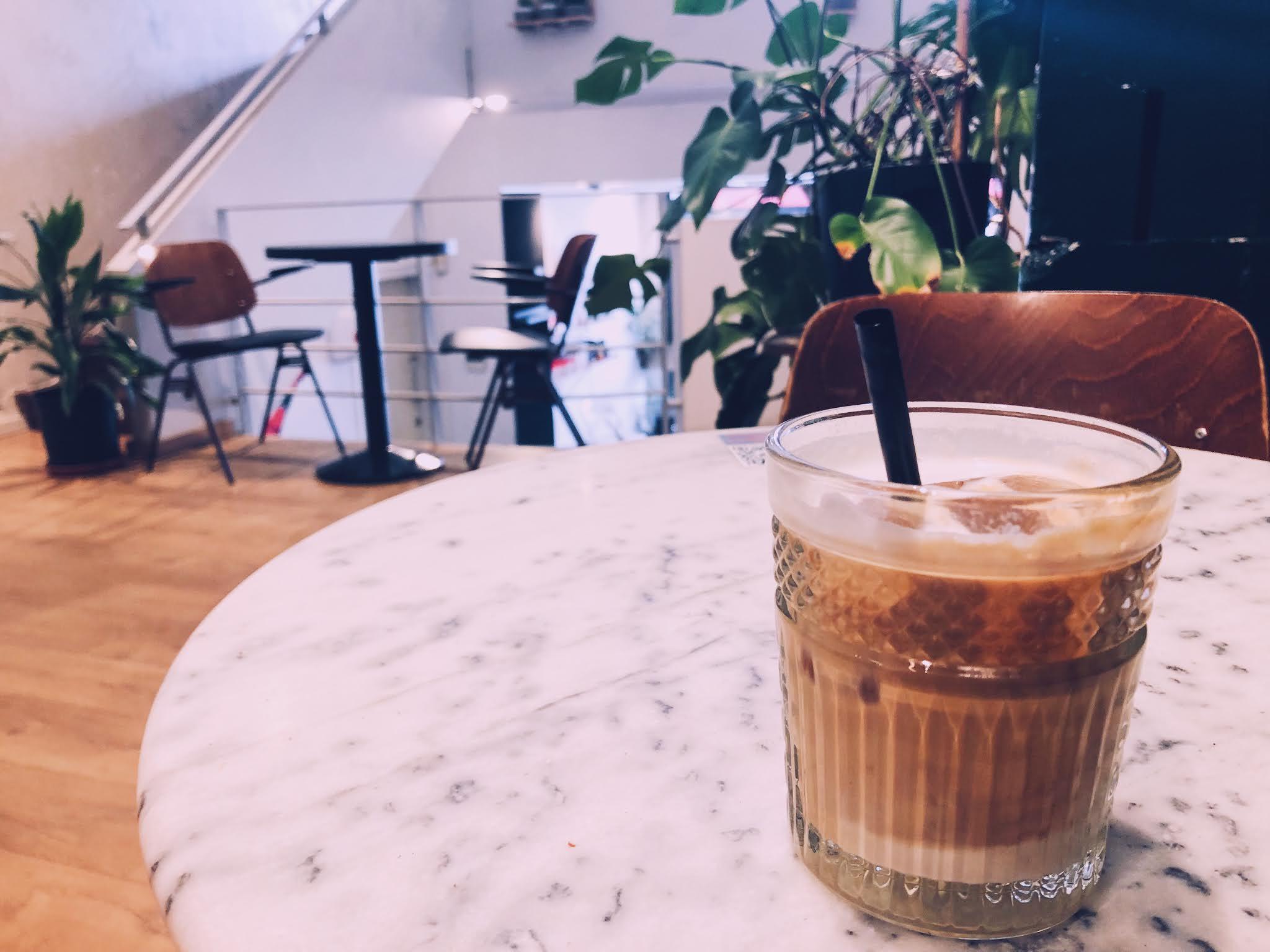 White iced coffee op een tafel in de Caffènation.