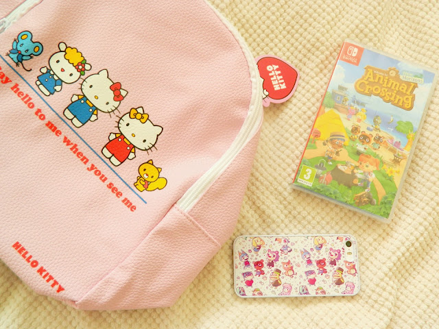 A photograph showing a pink hello kitty and friends backpack, along with an Animal Crossing: New Horizons game and phone case