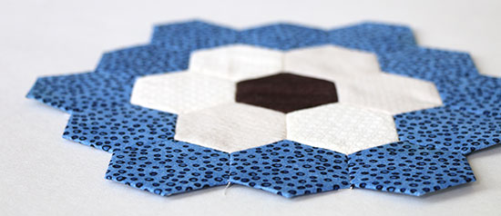 Angled view of a hand sewn EPP hexagon flower block in blue, off-white and dark brown on a white background.