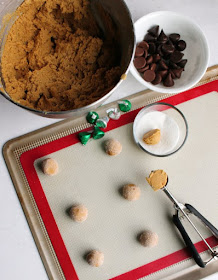bowl of peanut butter cookie dough being rolled into balls to become blossom cookies