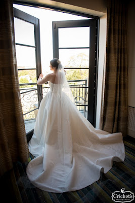 bride in white dress looking out window