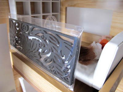 A laser-cut wooden bookmark-sized black panel leaning on the top of a one-twelfth scale doll's house mezzanine wall.