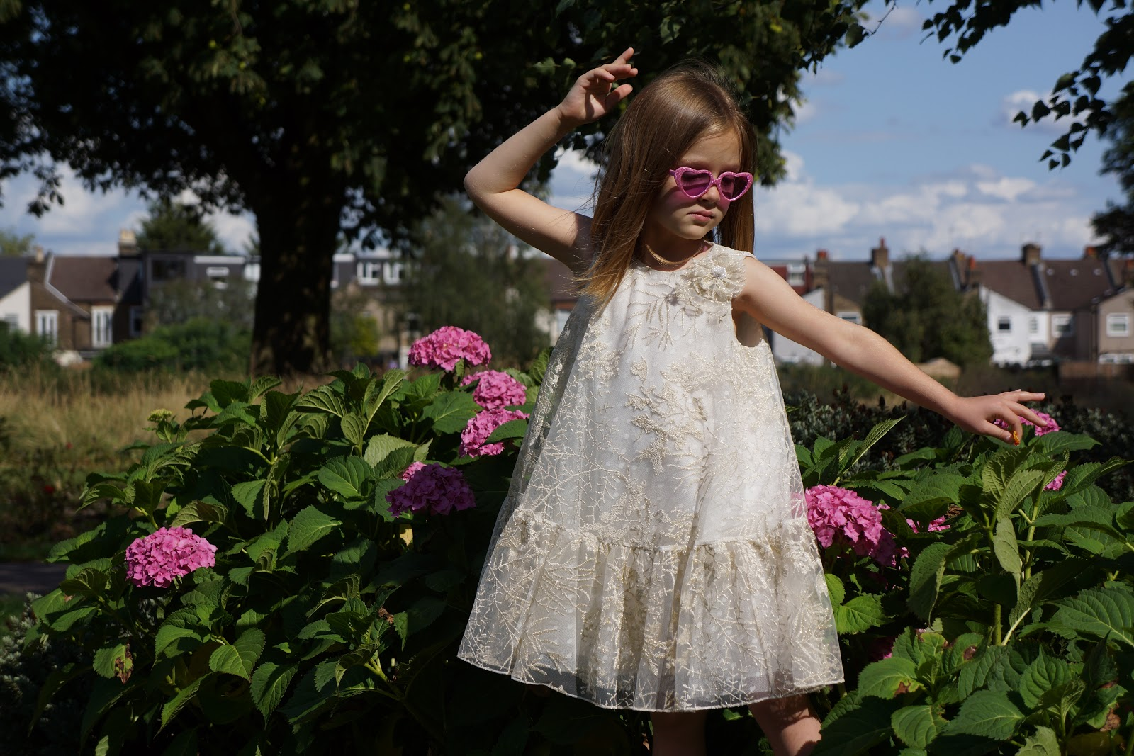 girl in pink heart sunglasses, David Charles Childrenswear gold and cream shift dress, in front of pink flowers