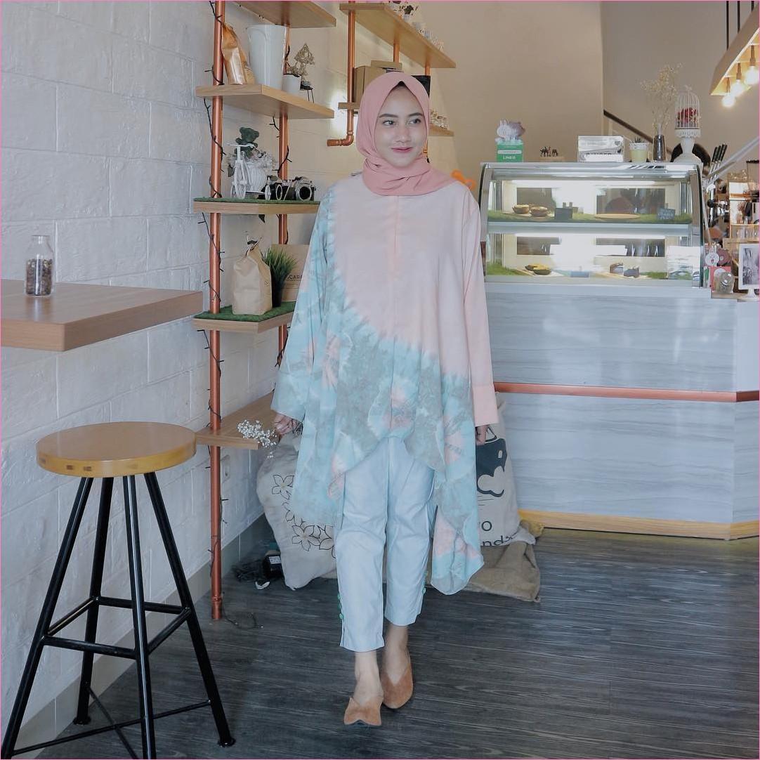 Outfit Baju Tunic Untuk Hijabers Ala Selebgram 2018 baju tunic bermotif bunga warna oren muda jeans denim biru muda flatshoes bulu krem hijab pashmina diamond baby pink ootd trendy kekinian cafe bangku kayu rak